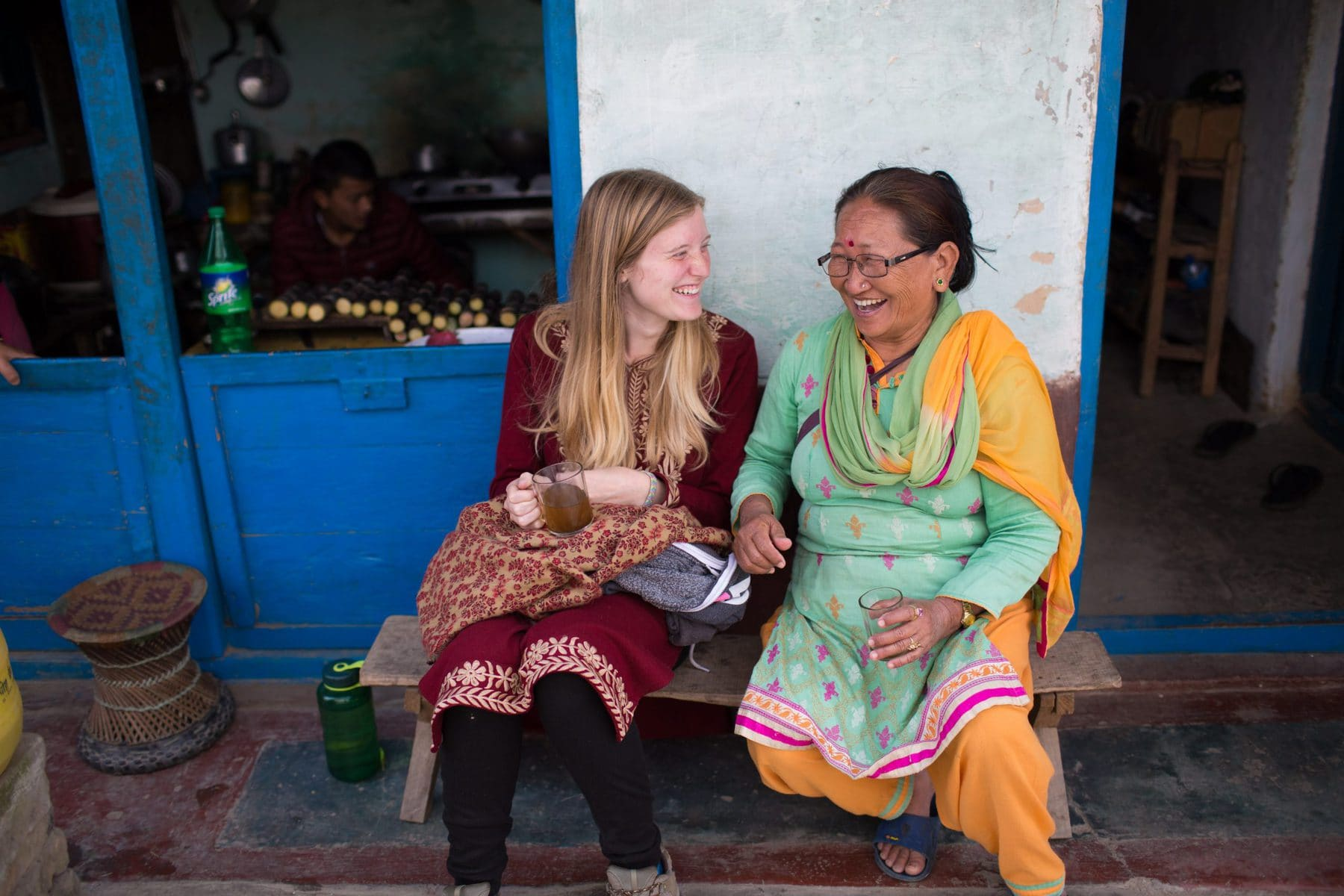 Missionary and her local friend dressed up in traditional clothes, having a cup of tea