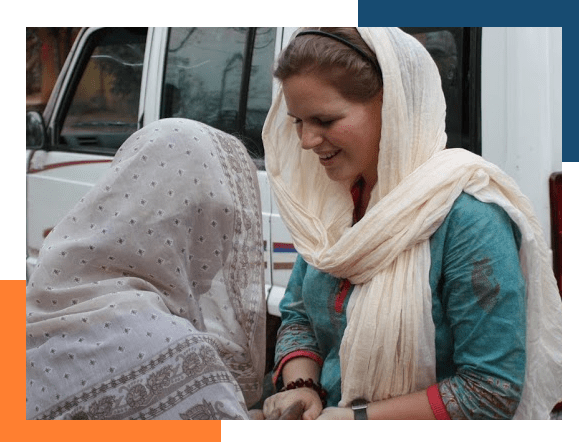 Missionary in a headscarf, covered by our international medical insurance, greeting a woman